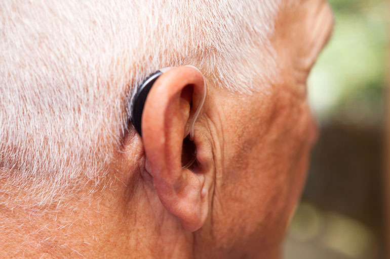 A senior man's ear with with a very modern, low-profile and discrete hearing aid. This is a behind-the-ear, open-ear style of hearing aid and represents the latest in hearing aid technology. Focus is on the area where the tube enters the ear, the back of the ear and over-ear portion of the hearing aid are slightly soft at 100%.